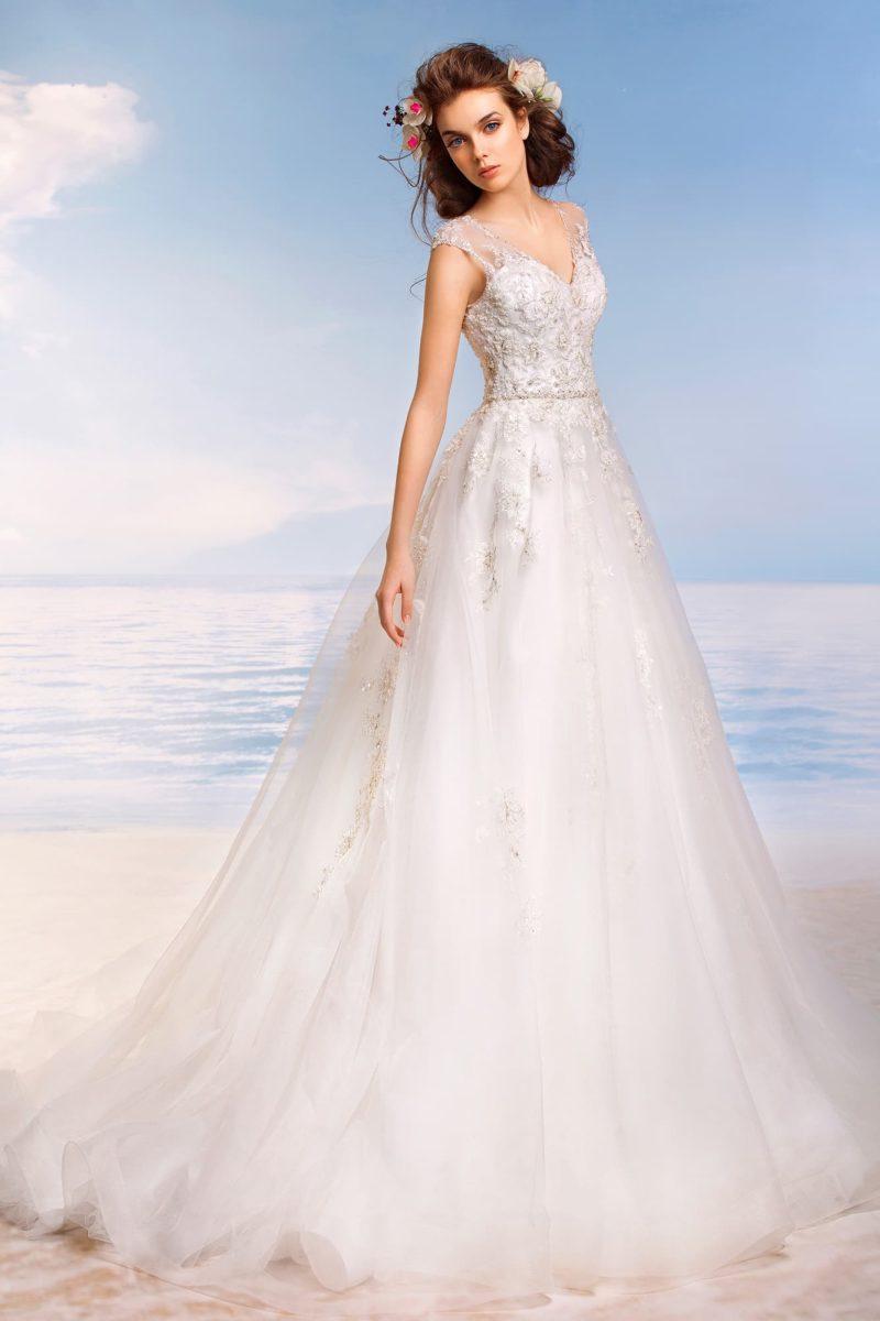 Пышное свадебное платье с полупрозрачной спинкой и закрытым лифом, украшенным кружевом.
