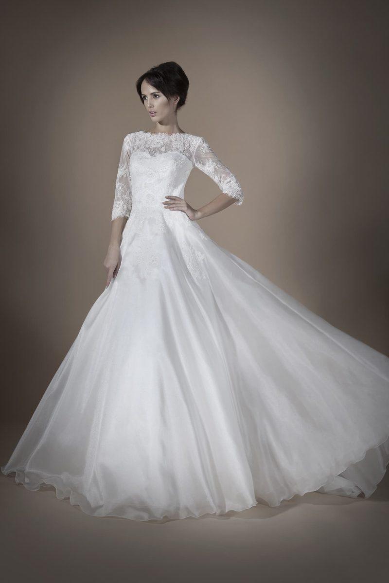 Закрытое свадебное платье с облегающими рукавами, небольшим вырезом на спинке и многослойной юбкой.