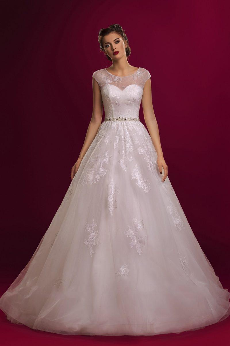 Закрытое свадебное платье с округлым вырезом и узким бисерным поясом, украшенное  кружевом.