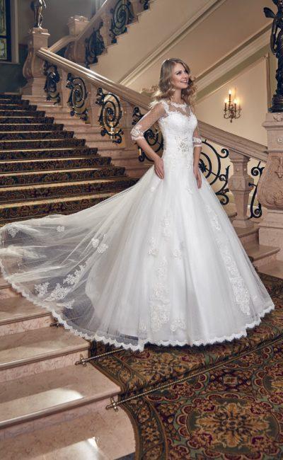 Закрытое свадебное платье с полупрозрачными рукавами и пышной юбкой с длинным шлейфом.