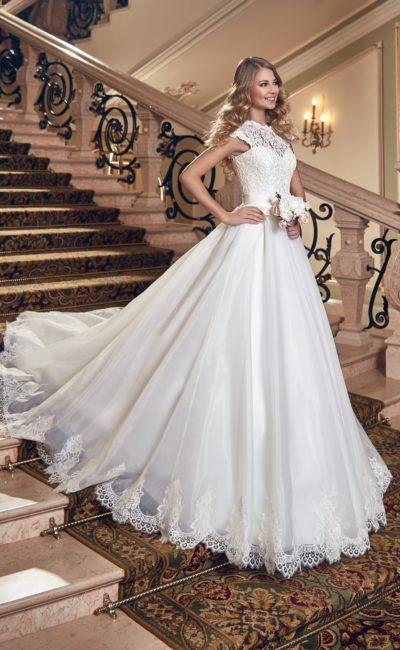 Великолепное свадебное платье с воздушной юбкой, декорированной кружевом, и закрытым верхом.