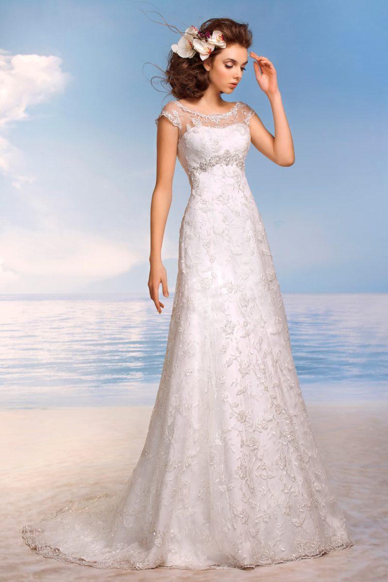 Кружевное свадебное платье с прямым силуэтом и слегка завышенной линией талии, выделенной бисерным поясом.