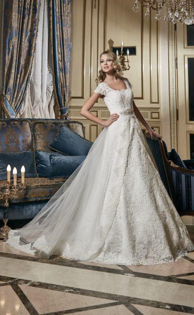 Роскошное свадебное платье с прозрачной верхней юбкой и кружевным декором по всей длине.