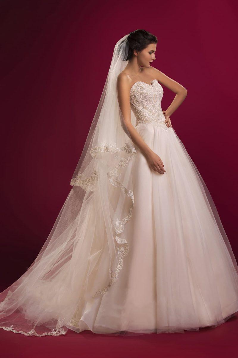 Торжественное свадебное платье с многослойным подолом юбки со шлейфом и открытым кружевным корсетом.