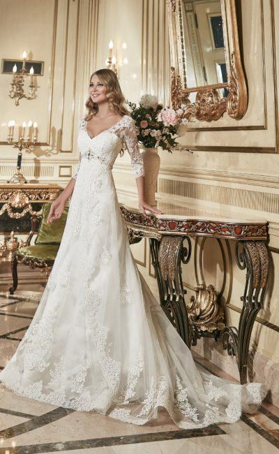 Свадебное платье с юбкой «трапеция», дополненной прозрачной тканью с кружевной отделкой.