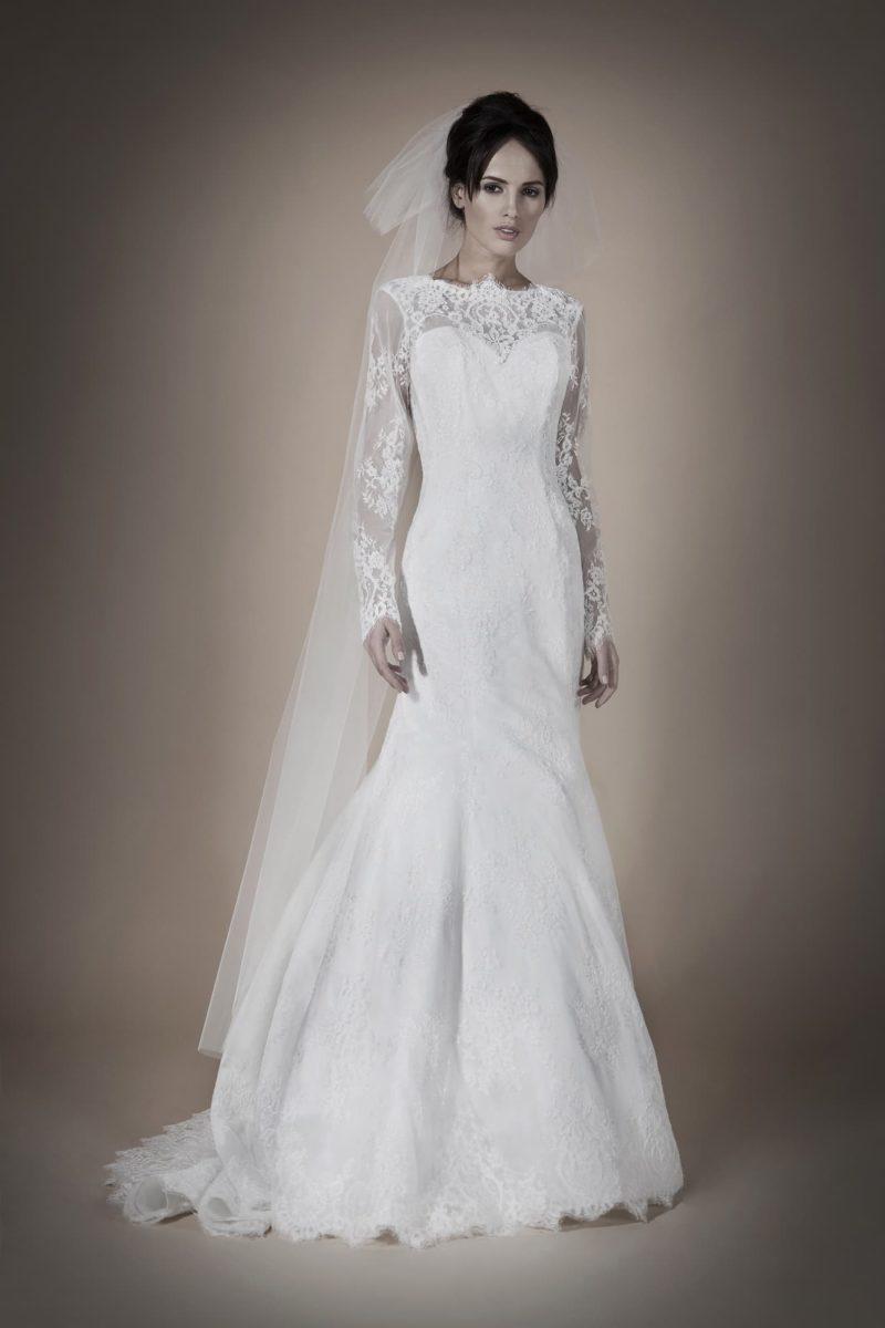 Сдержанное свадебное платье силуэта «русалка» с длинным рукавом из плотной кружевной ткани.