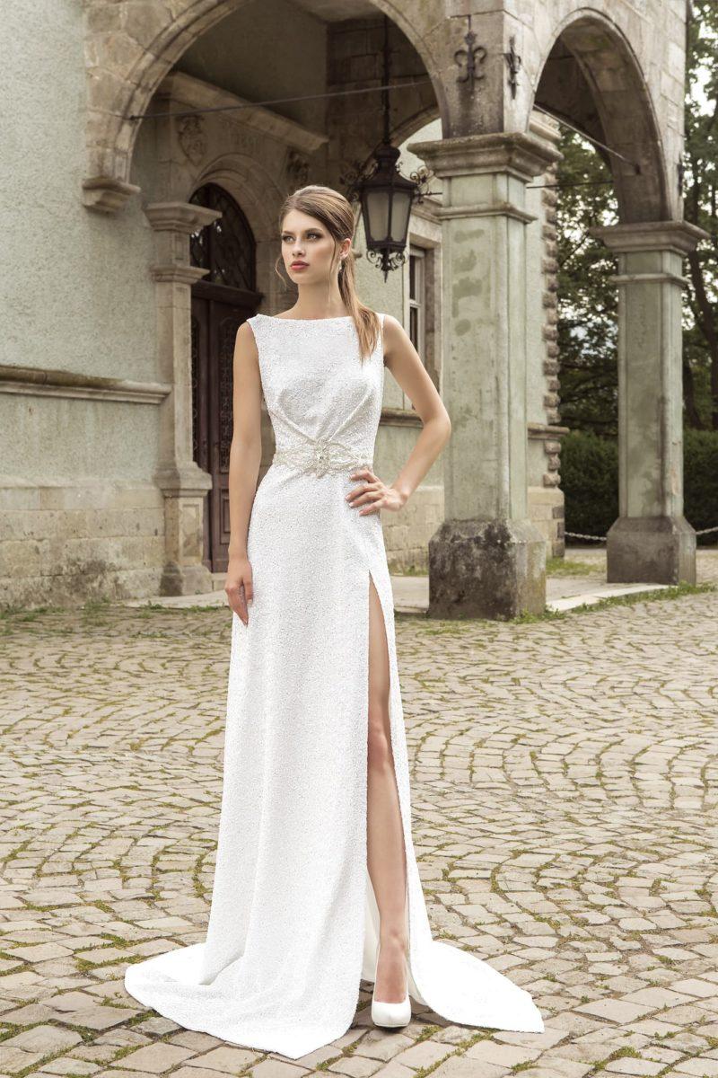 Прямое свадебное платье из фактурной ткани, с вырезом бато и соблазнительным разрезом по подолу.