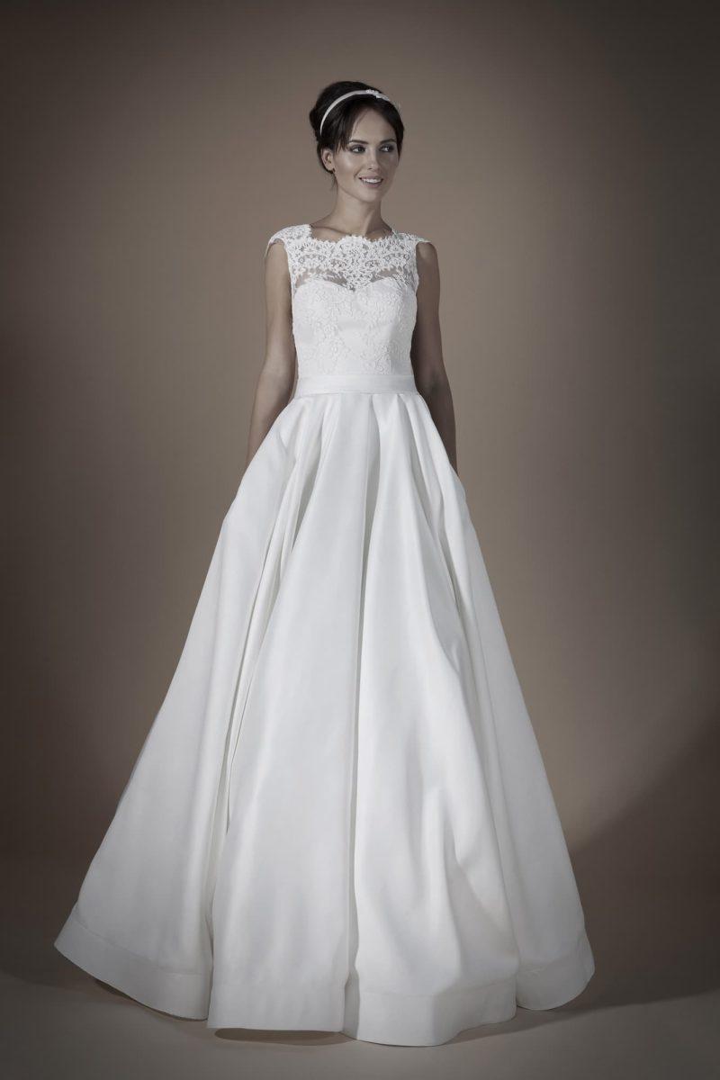 Атласное свадебное платье с кружевным закрытым верхом и пышной юбкой с небольшим шлейфом.