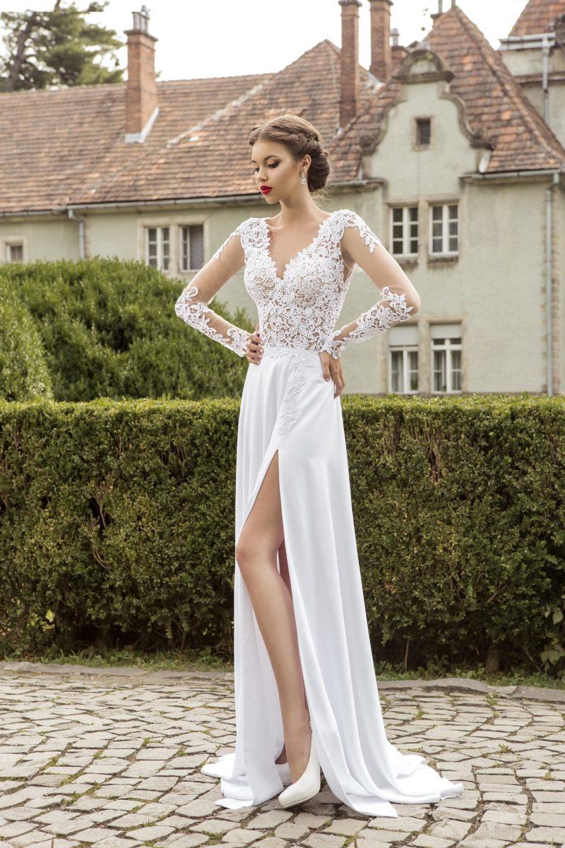 Свадебное платье «колонна» с полупрозрачным кружевным верхом и драматичным разрезом на юбке.
