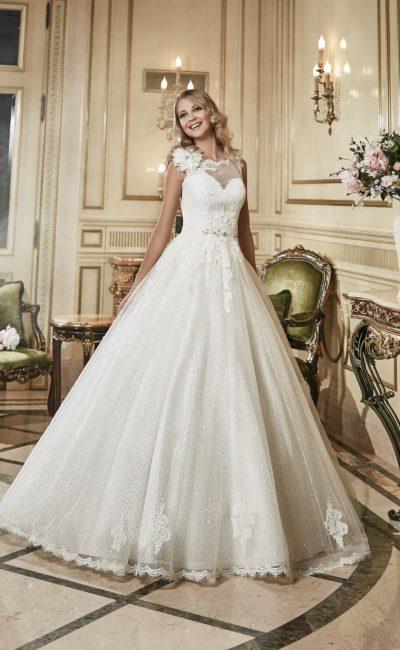 Сияющее свадебное платье с отделкой пайетками и пышным бутоном на плече закрытого лифа.