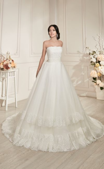 Свадебное платье пышного кроя с открытым корсетом и горизонтальными полосами декора на юбке.