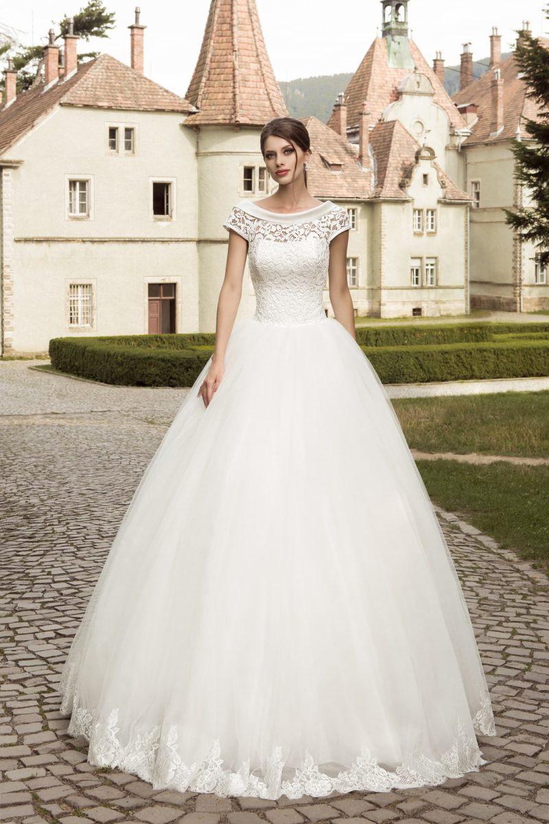 Пышное свадебное платье с кружевным декором корсета и округлым вырезом, оформленным атласом.