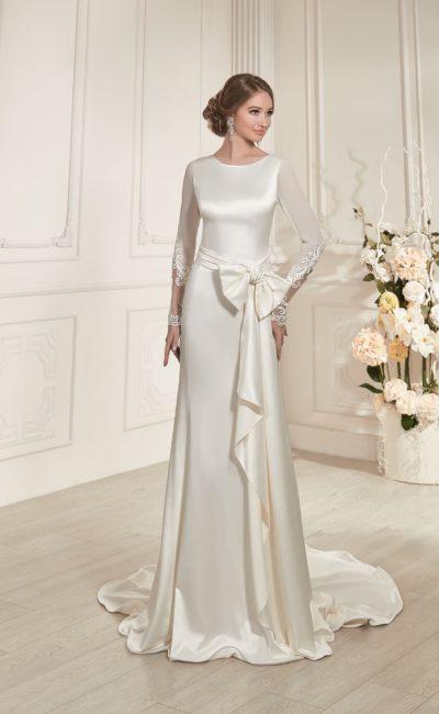 Изысканное свадебное платье прямого кроя из сияющего атласа, с длинными полупрозрачными рукавами.