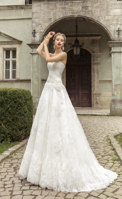 Свадебное платье «принцесса» с драпировками на корсете и аппликациями на многослойной юбке.