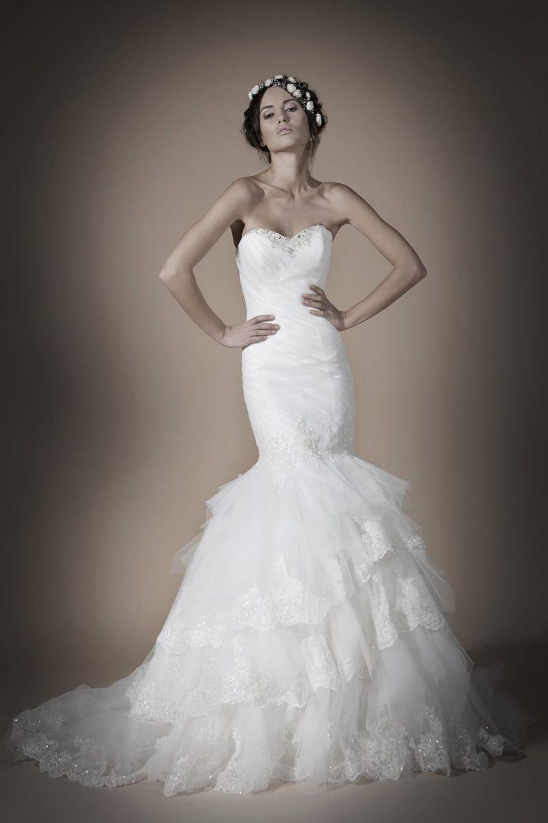 Свадебное платье с открытым лифом с сияющей отделкой и низом подола, покрытым оборками.