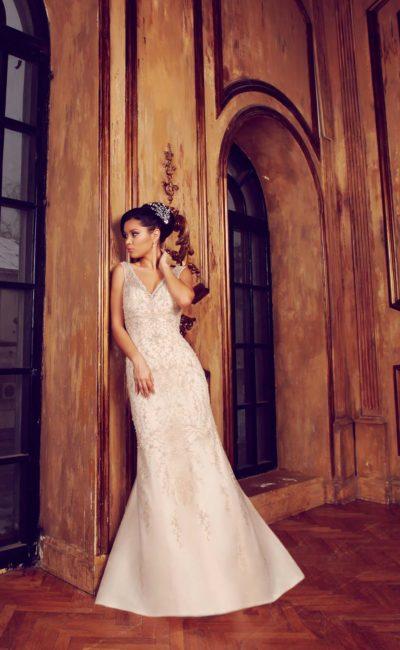 Свадебное платье с V-образным вырезом, кружевным декором и деликатным шлейфом сзади.