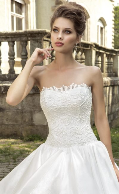 Романтичное свадебное платье пышного кроя, подчеркивающее декольте прямым лифом.
