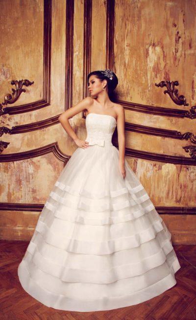 Притягательное свадебное платье с горизонтальными полосами отделки по пышному подолу.