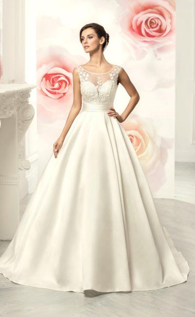 Свадебное платье с пышной атласной юбкой и драматичным V-образным вырезом на спинке.