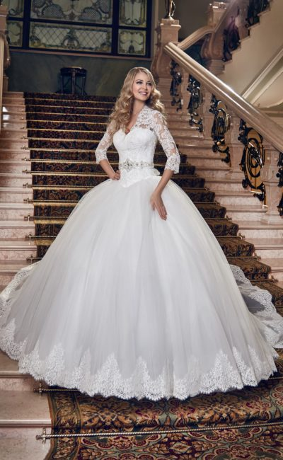 Пышное свадебное платье с V-образным декольте и широким поясом на талии.