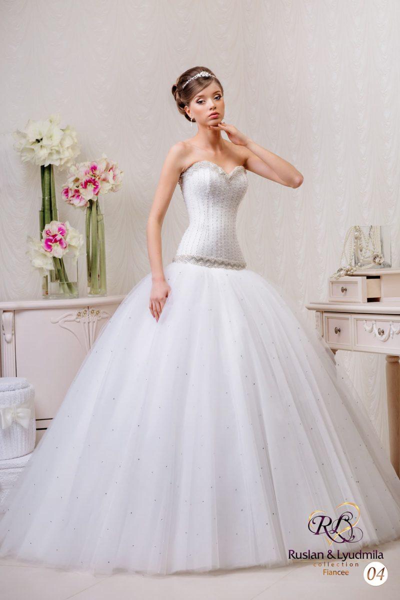 Свадебное платье с полностью расшитым бисером корсетом и многослойной юбкой.