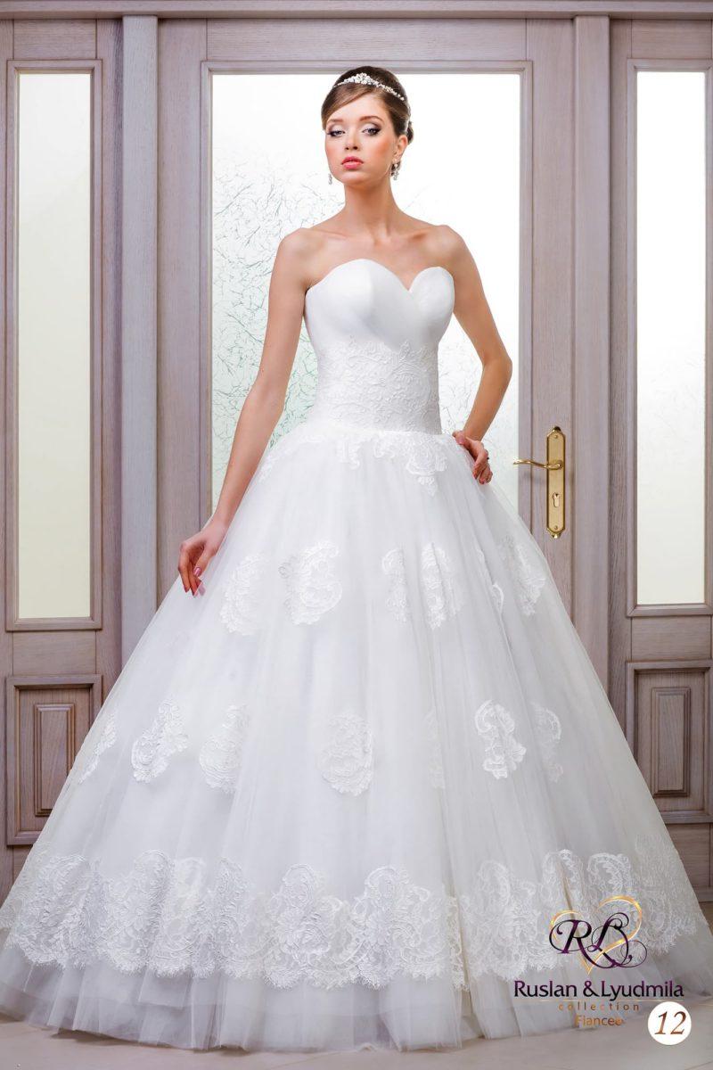 Романтичное свадебное платье с открытым лифом в форме сердца и кружевным декором низа.