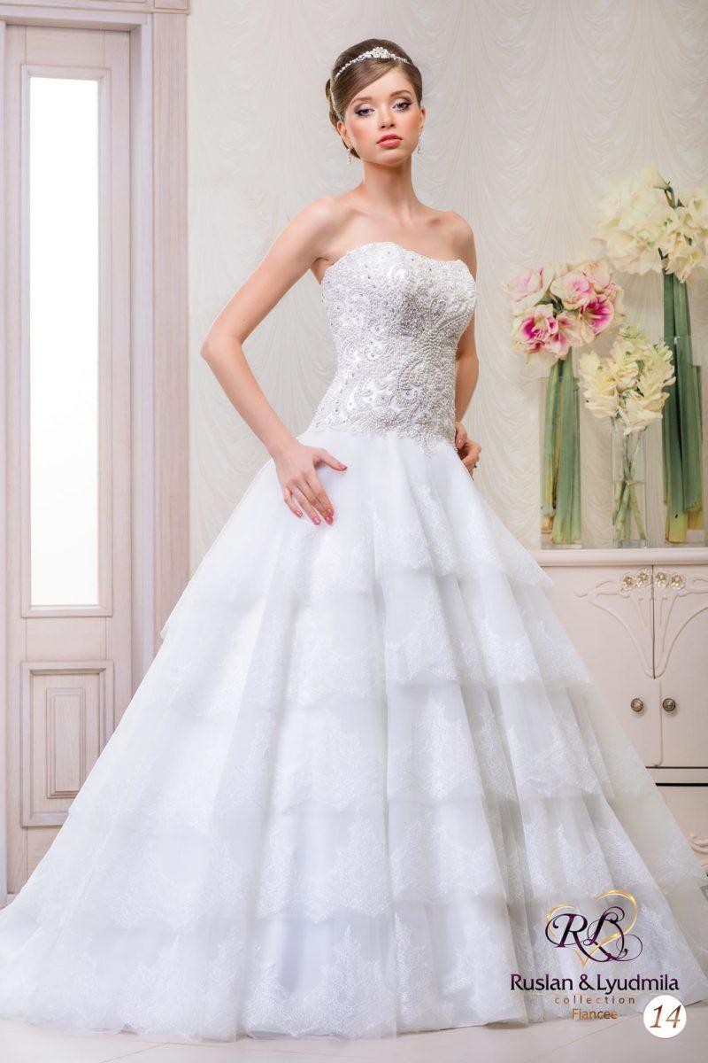 Свадебное платье А-силуэта с многоуровневой юбкой и классическим открытым верхом.