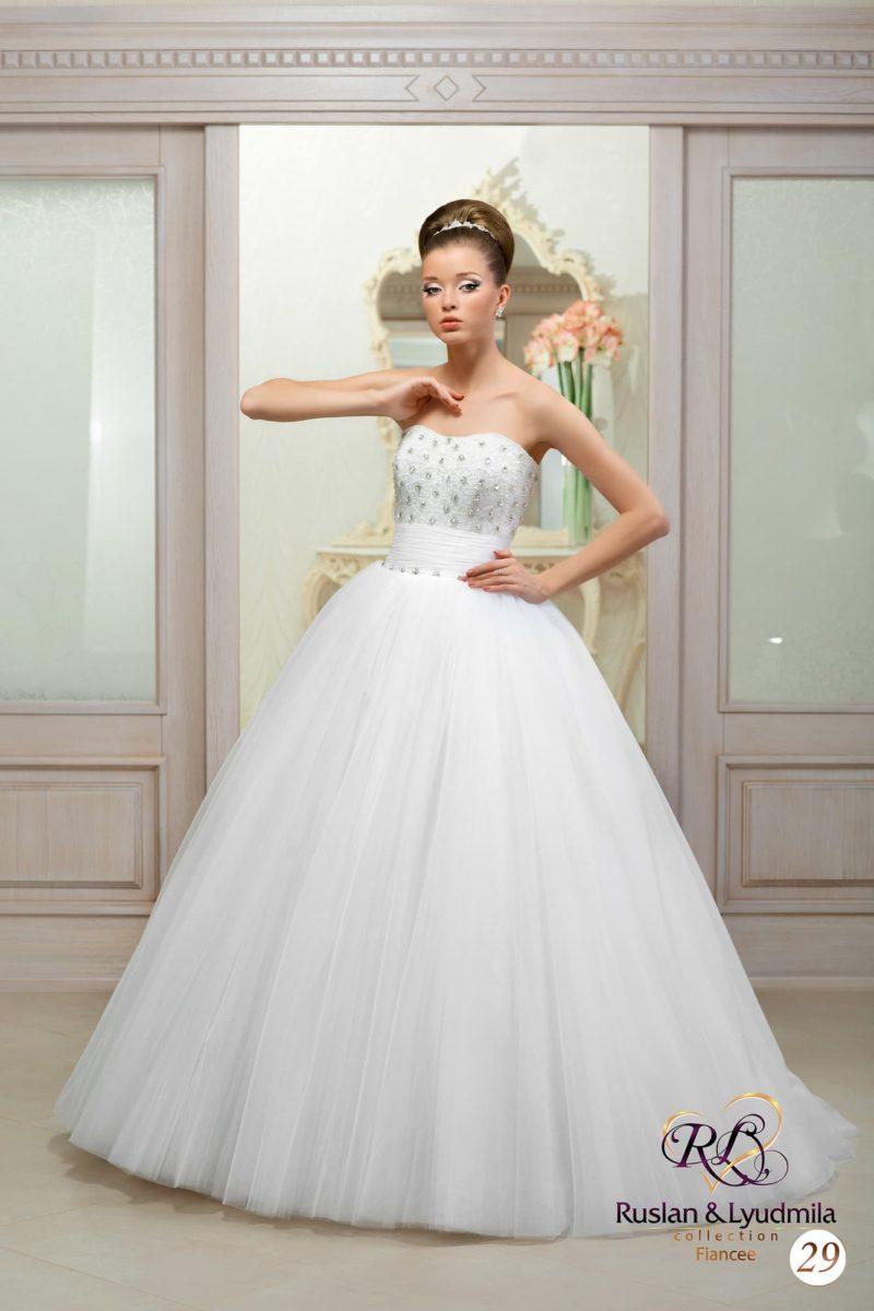 Стильное свадебное платье с открытым лифом деликатного кроя, украшенным серебристой вышивкой.