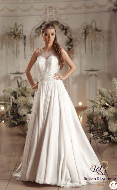 Деликатное свадебное платье с полупрозрачной вставкой над лифом и элегантной юбкой.