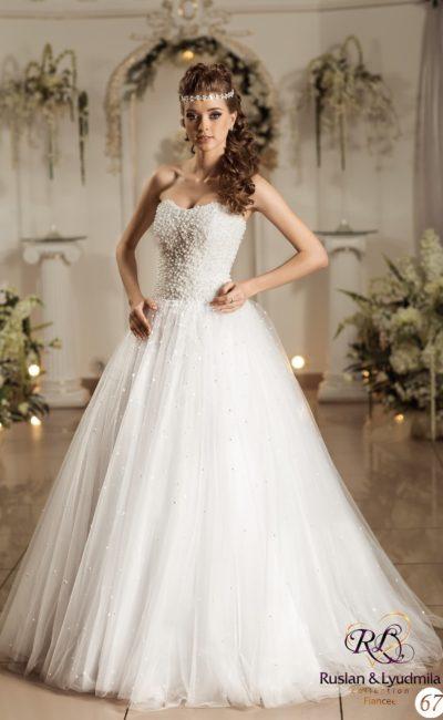 Свадебное платье с многослойной юбкой «трапеция» и открытым корсетом, покрытым бусинами.