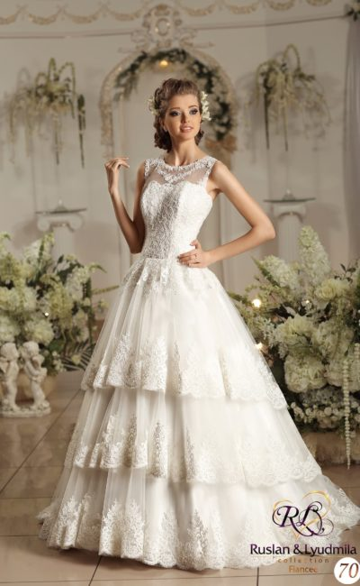 Кокетливое свадебное платье кроя «трапеция» с кружевным декором верха и многоуровневой юбкой.