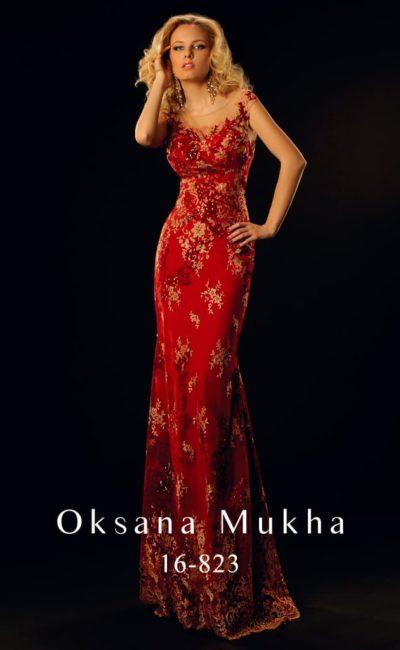 Ярко-красное вечернее платье облегающего кроя, украшенное золотистым кружевом.