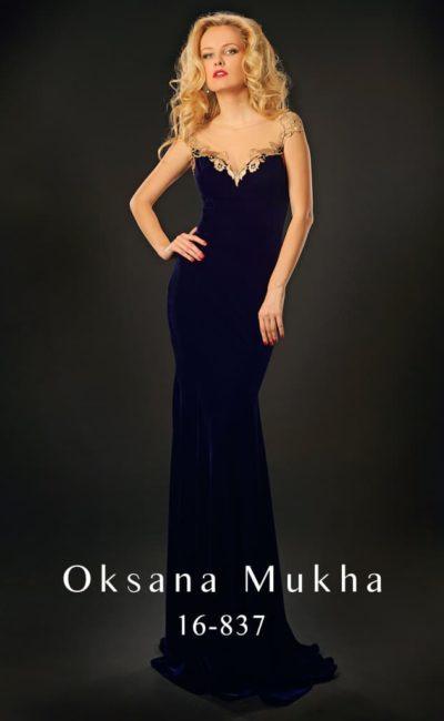 Бархатное вечернее платье синего цвета с золотистым декором лифа и открытой спинки.