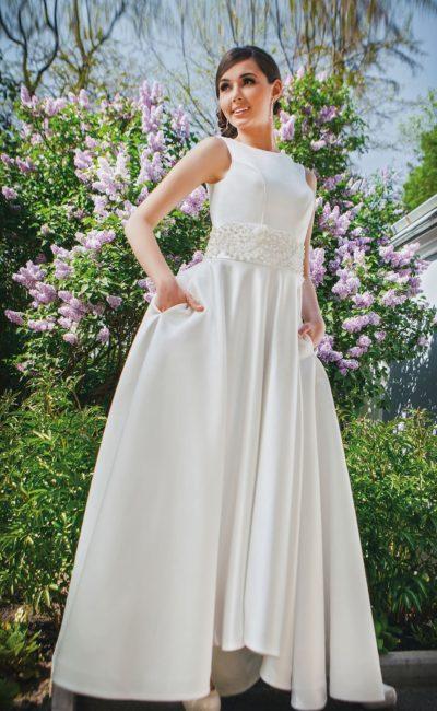 Закрытое свадебное платье с широким поясом, украшенным бисером, и стильным вырезом сзади.