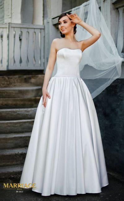Изысканное свадебное платье традиционного кроя, выполненное из сияющей атласной ткани.