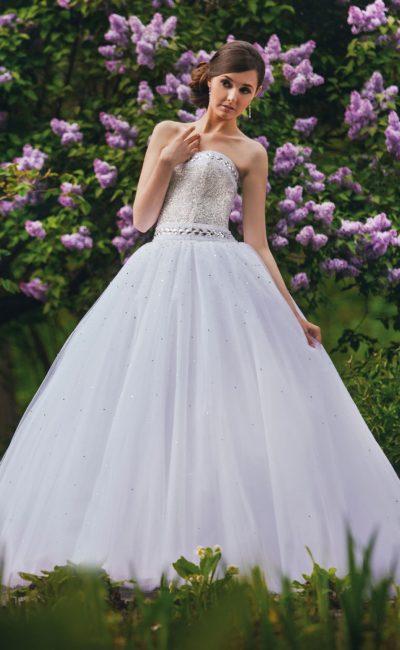 Свадебное платье с роскошной многослойной юбкой и открытым корсетом, покрытым стразами.
