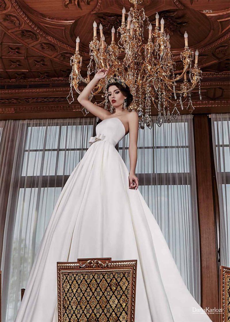 Атласное свадебное платье с открытым корсетом прямого кроя и объемной юбкой с длинным шлейфом.
