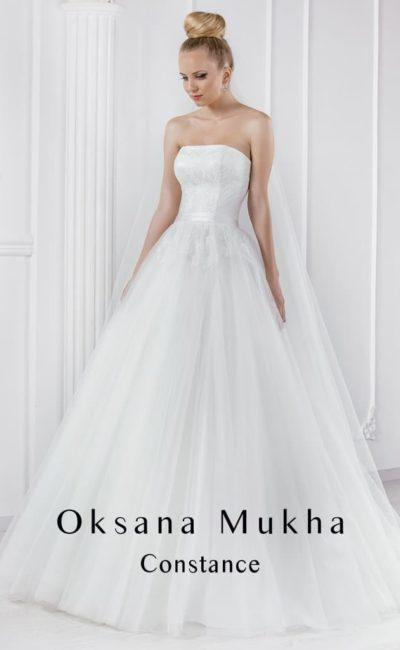 Изысканное свадебное платье с открытым лифом и многослойной юбкой.