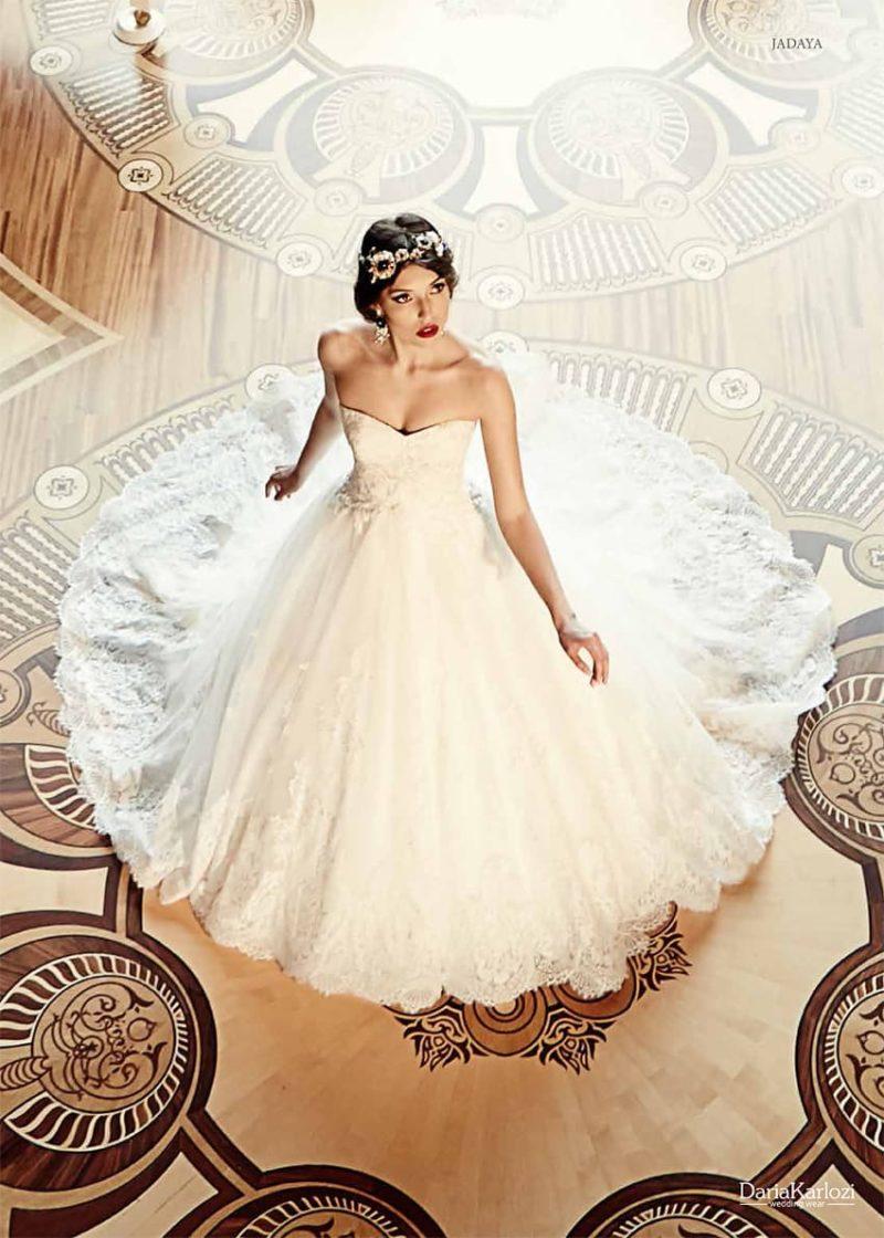 Кружевное свадебное платье с многослойным подолом и открытым лифом в форме сердца.