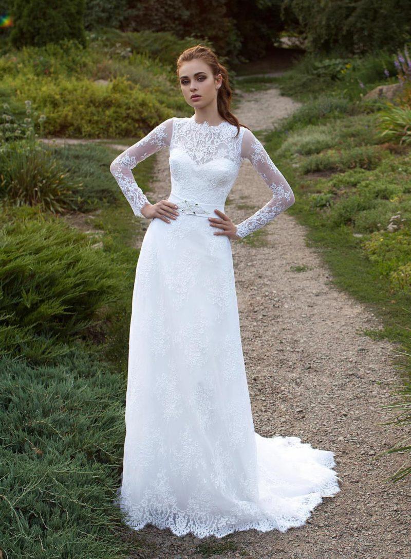 Оригинальное свадебное платье прямого кроя, покрытое кружевной отделкой, с длинным рукавом.