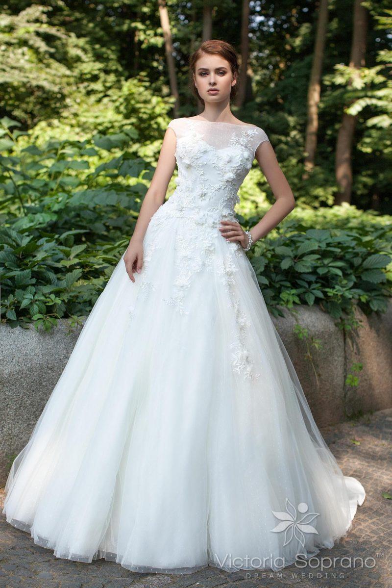 Закрытое свадебное платье с многослойным подолом и объемной отделкой закрытого верха.