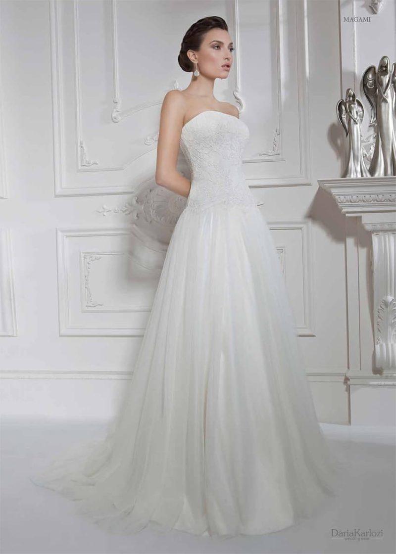 Свадебное платье с многослойной пышной юбкой и лаконичным кружевным корсетом.