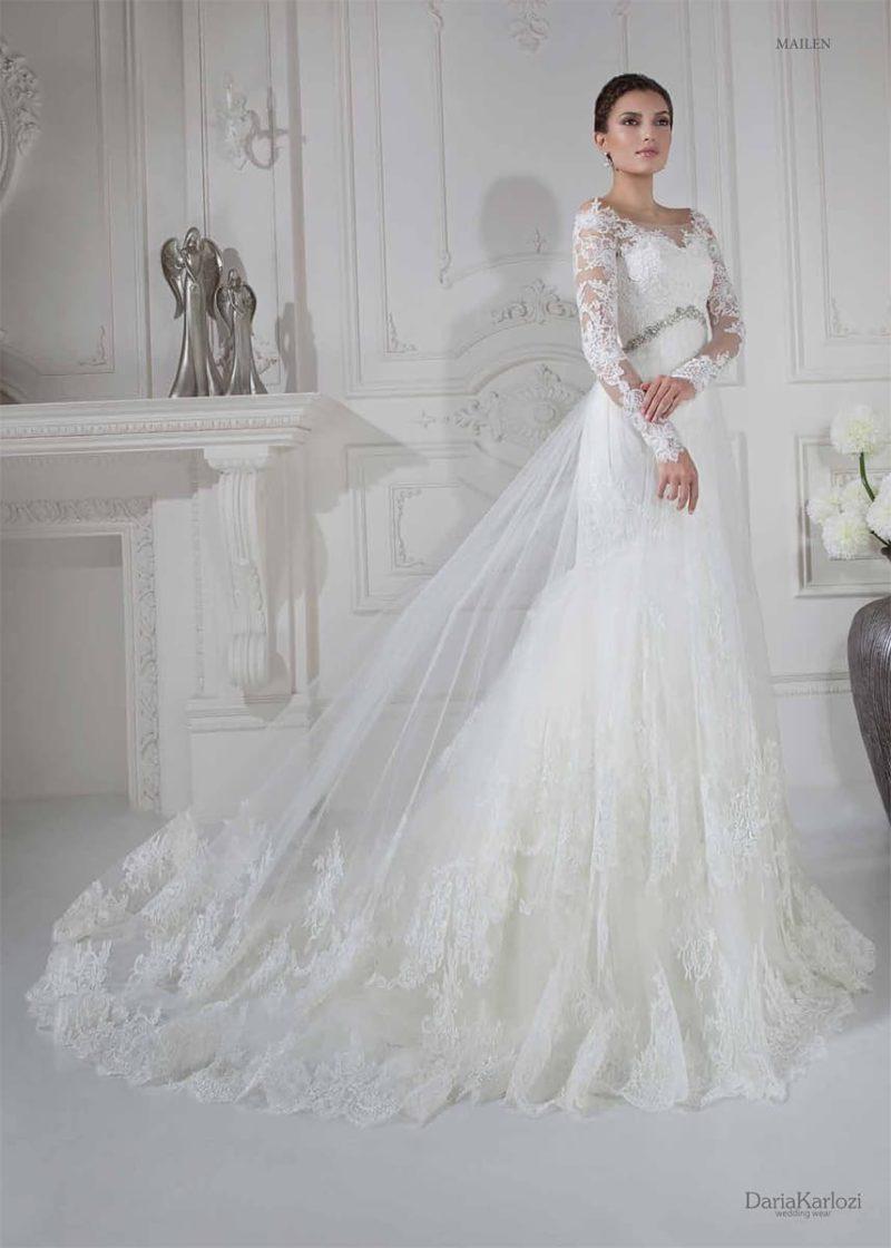 Пышное свадебное платье с прозрачной верхней юбкой и длинными кружевными рукавами.