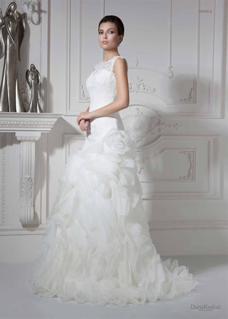 Необычное свадебное платье с закрытым лифом и объемной отделкой по юбке со шлейфом.
