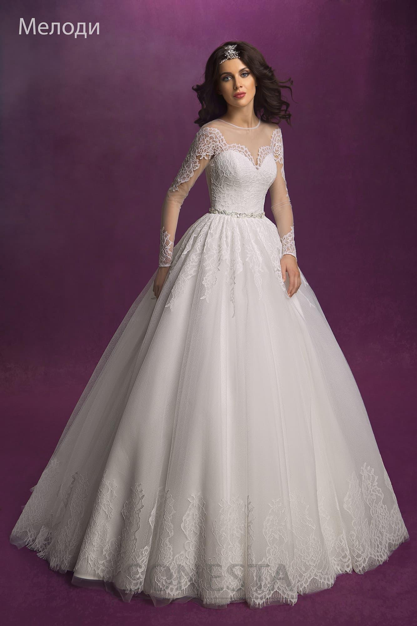 57680074a15 Пышное свадебное платье с длинными полупрозрачными рукавами и кружевным  декором подола.