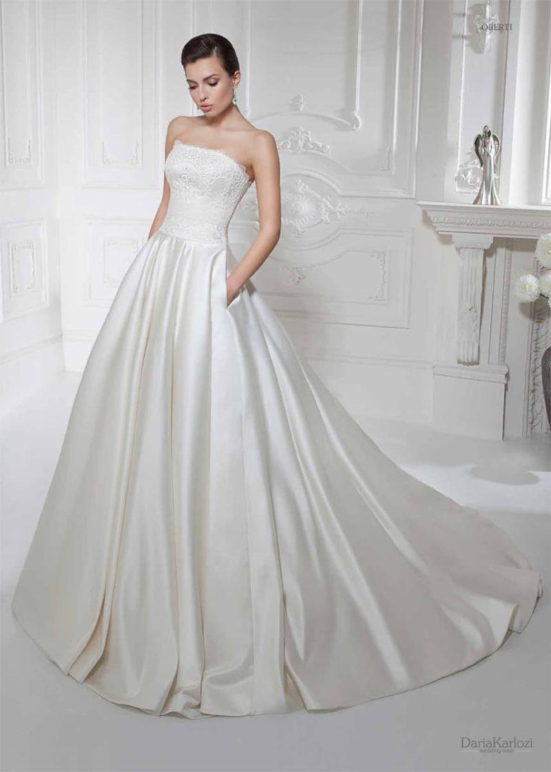 Свадебное платье с кружевным корсетом и атласной юбкой, дополненной скрытыми карманами.