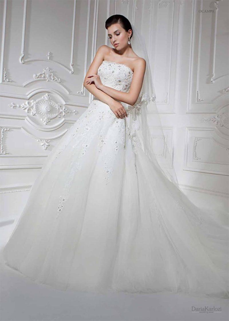 Сдержанное свадебное платье в торжественном стиле, с открытым корсетом, украшенным вышивкой.