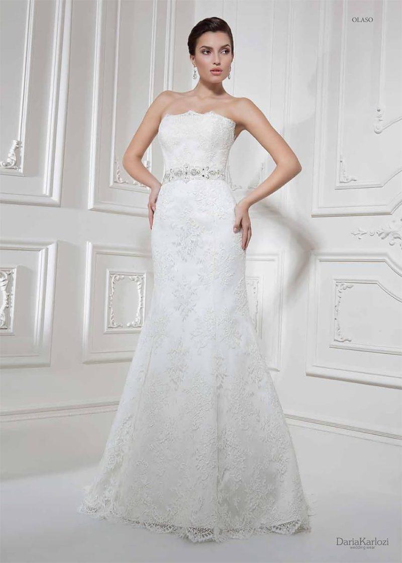 Деликатное свадебное платье облегающего кроя, покрытое кружевной отделкой.