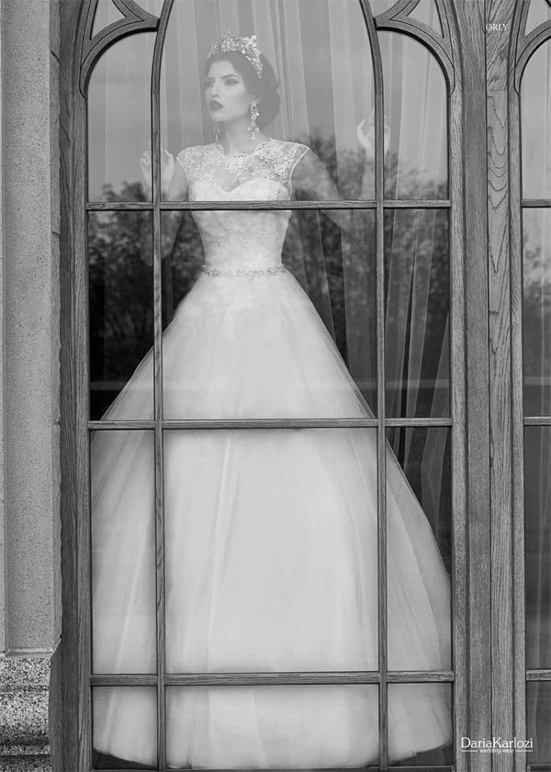 Пышное свадебное платье с округлым кружевным вырезом и элегантным узким поясом.