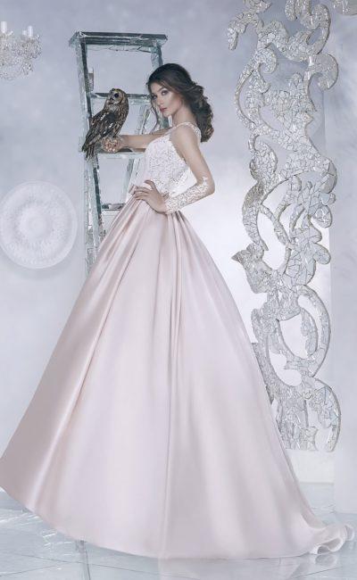 Кремовое свадебное платье с пышной атласной юбкой и полупрозрачными длинными рукавами.